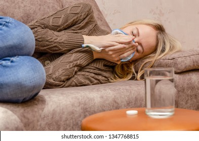 blonde girl sitting on the couch. She has a runny nose, so she blows her nose and wipes away tissue paper. place the medicine and a glass of water on the table next to it. The concept of the disease