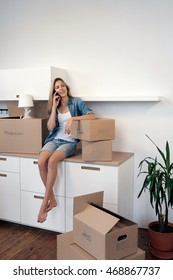 Blonde girl sitting on kitchen counter and talking over phone .Copy space