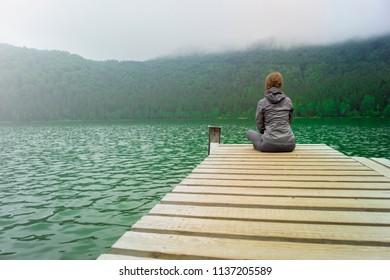 Blonde girl sitting on lakeside jetty