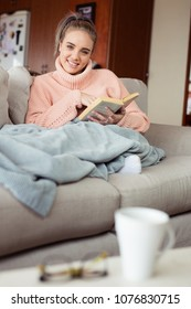 Blonde girl sitting on a sofa with a book in her hand while she is looking straight int the camera.