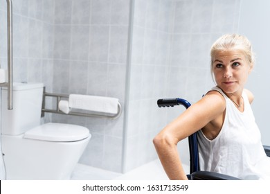 Blonde girl sitting in a wheelchair in a bathroom with the toilet behind her with her head turned sideways