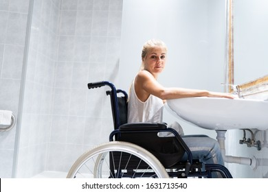 Blonde girl sitting in a wheelchair in front of a sink in a bathroom with her head turned sideways