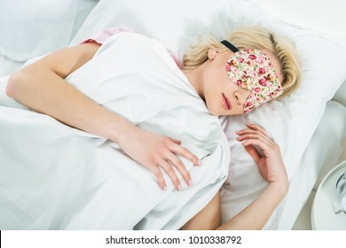 blonde girl in sleeping mask on bed