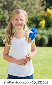 Blonde girl smiling and holding pinwheel in the park on sunny day