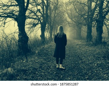 Blonde girl standing back and looking to a gloomy linden alley in autumn. Misty and dreamy alley with bare trees and fall leaves on the ground. Dark, negative thoughts and feeling anxious, stressed.