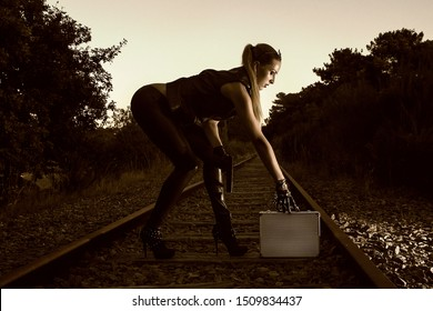 Blonde girl with suitcase on the background of an abandoned railway. Sexy woman in black leather clothes with gun at night. Criminal gangsta woman escape from mafia. Spy with weapon.