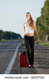blonde girl with suitcase on the road