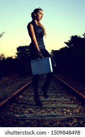 Blonde girl with suitcase walking by the abandoned railway. Sexy woman in black leather clothes with gun at night. Criminal gangsta woman escape from mafia. Spy with weapon.