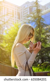 A  blonde girl in sunglasses paints her lips with red lipstick on high-rise buildings. A woman is applying makeup.