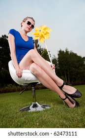 blonde girl with sunglasses and a pinwheel on a swivel chair