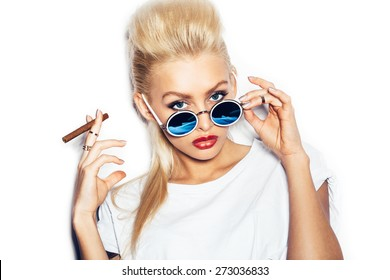 Blonde girl in sunglasses and white t-shirt smoking cigar.  White background, not isolated