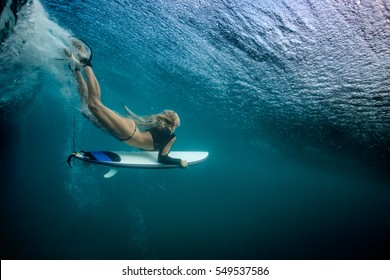 Blonde girl Surfer holding white surf board Diving Duckdive under Big Beautiful Ocean Wave. Turbulent tube with air bubbles and tracks after sea wave crashing. Ripples at water surface with blue color