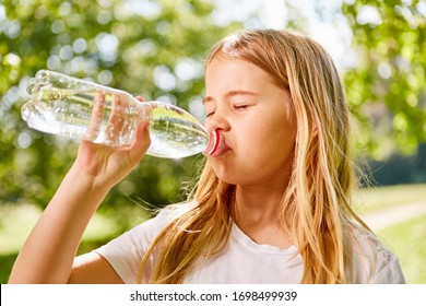 Blonde girl is thirsty and drinks mineral water from a bottle