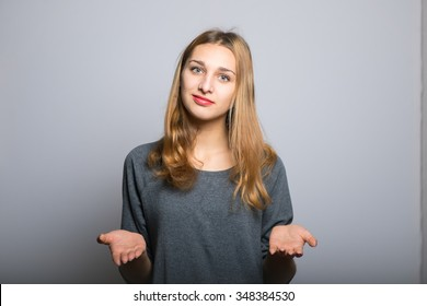 blonde girl throws up his hands, with clean skin, lifestyle concept studio photo isolated on a gray background