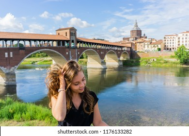 Blonde girl touching her hair and smiling near Ponte Coperto in Pavia, Lombardy, Italy