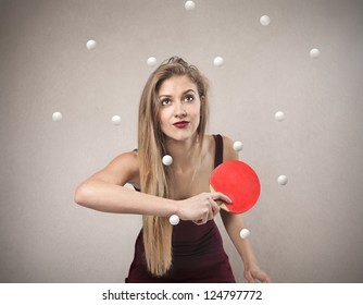 Blonde girl trying to hit a ball with a ping pong racket