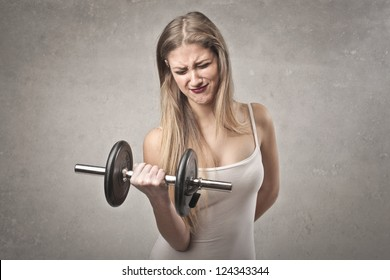 Blonde girl trying to raise a dumbbell