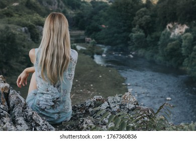 Blonde girl with turn back sitting on the rocks and looking at the river