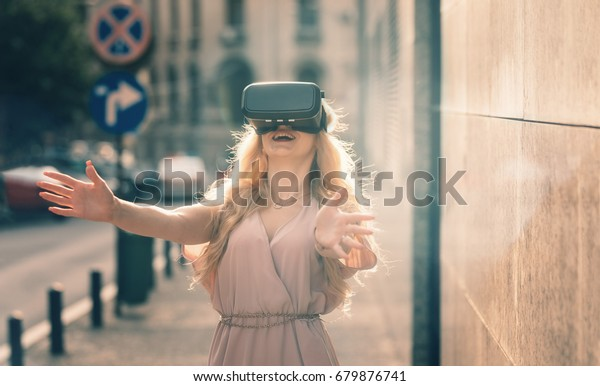 Blonde girl using cool VR set to experience living in fantasy computer game left amazing sights of the fantasy location Oculus VR technology VR gear Digital 3D video VR headset 360 video business
