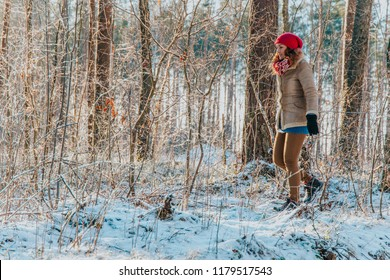Blonde girl walking between branches in snowy winter forest with warm sunlight