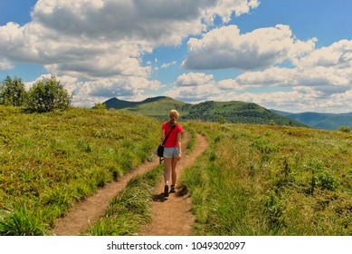 Blonde girl walking on a trail leading to mountain peaks. Fit woman hiking in the mountains. Summer free time sport recreation. Shorts and t-shirt, cloudy sky and green grass. Blooming nature outdoors