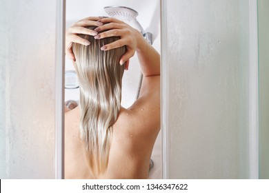 Blonde girl washes her hair in the shower back view