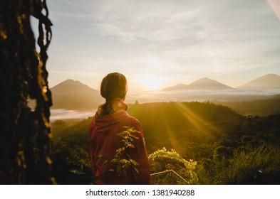 Blonde girl watching sunrise at viewpoint over Batur Global Geopark, Kintamani, Bali, Indonesia