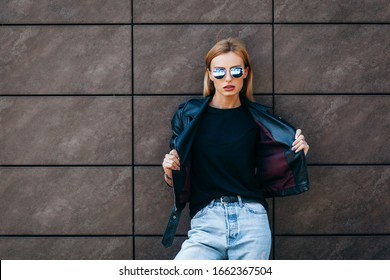 Blonde girl wearing black t-shirt, glasses and leather jacket posing against street , urban clothing style. Street photography