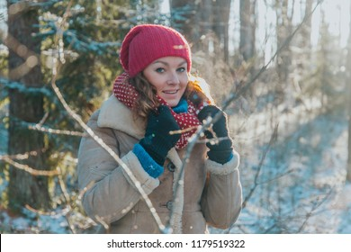 Blonde girl wearing hat and gloves inside winter forest with snow with warm sunset light