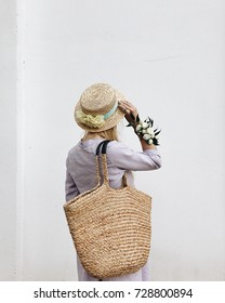 Blonde girl wearing long linen dress and straw hat with flowers on the hand walking in the city, holding beautiful straw bag. Lifestyle concept.