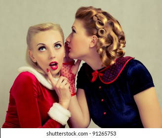 blonde girl whispers to her friend's ear