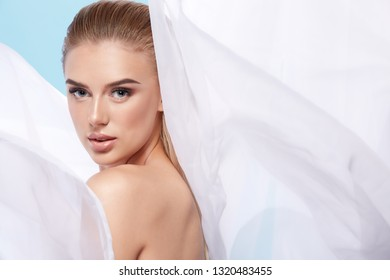 Blonde girl at white background wearing dress and nude make up, portrait. Girl with wet hair and blue eyes. Make up model at white background.