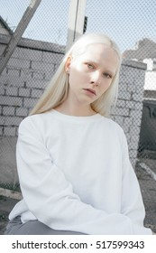 blonde girl with white eyebrows  around the gray walls.dressed in white with sparkling eyes.  fashion model test