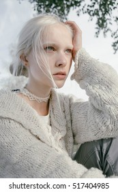blonde girl with white eyebrows .outdoors. dressed in white with sparkling eyes.  fashion model test