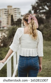 Blonde girl with a white shirt, a pony tale and a vintage hair tape from the back
