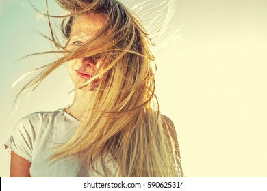 Blonde girl in windy day, with  her lond hairs fly with the wind shot with copyspace, retro color