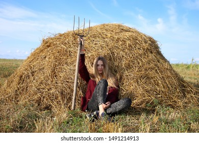 A blonde girl worker, sat down on a hay to rest after hard work in the field, with a pitchfork in her hands.