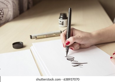 A blonde girl writes with a brush and ink, a letting process. Concept creativity and calligraphy