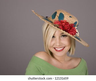 A blonde in a green blouse and a flowered hat with a nice smile