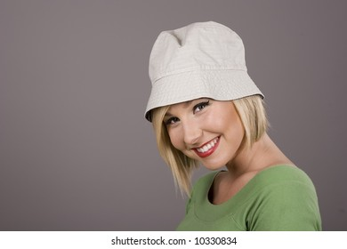 A blonde in a green blouse and white hat smiling for the camera