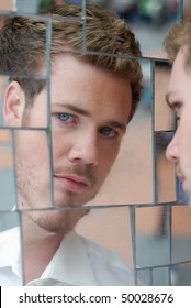 Blonde hair blue eyed man looking at his reflection in mirror