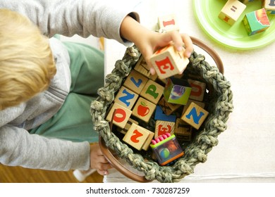 Blonde hair child playing with wooden cubes. Left hand holding. Daylight