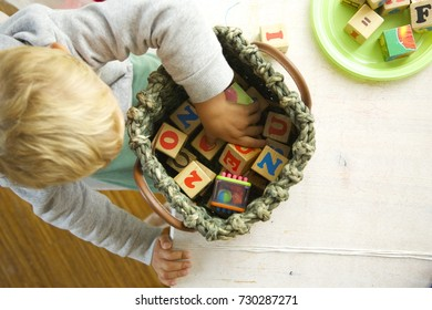 Blonde hair child playing with wooden cubes. White wooden table. Daylight
