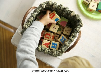 Blonde hair child playing with wooden cubes. One hand holding. Daylight