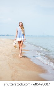 Blonde hair girl in the dress is walking on the coast