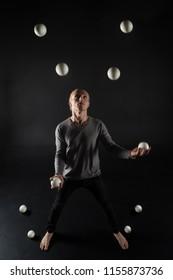 Blonde hair juggler with white balls on black background