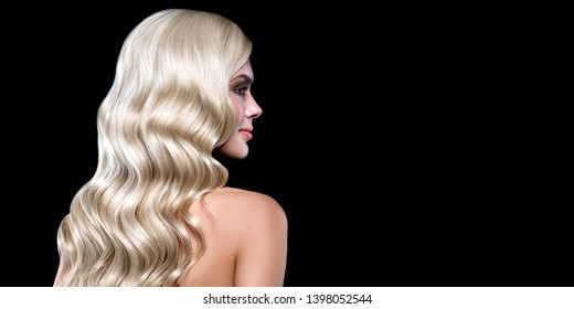 Blonde  Hair Portrait with blue eyes and Healthy Long Shiny Wavy hairstyle posing on black background. Volume shampoo. Blond Curly permed Hair and bright makeup.  Beauty salon and haircare concept.