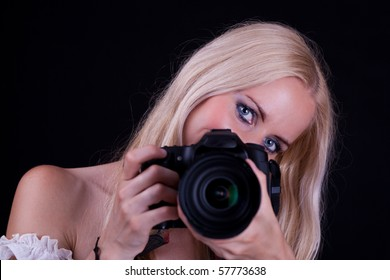 Blonde hair woman, holding camera aimed in front of you. Black Background.