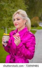 Blonde hair woman in a pink raincoat eats a donut and drinks coffee at park. Difficulties for diet. Cute girl on a diet struggles with a temptation to eat sweets