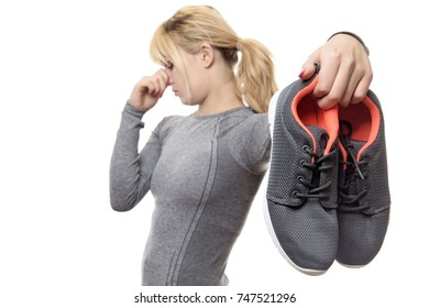 blonde haired woman holding up her smelly gym shoes